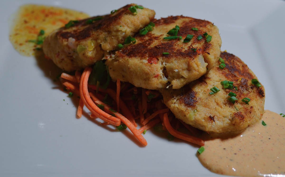 crab cakes on plate with sauce and garnish