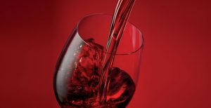 Red wine being poured into a wine glass against a red background.