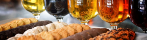 Gasses of beer and Girl Scout cookies lined up on a table.
