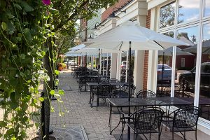 The outdoor patio with tables, chairs and umbrellas set up at Napa Montgomery