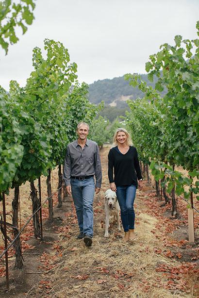 Joel and Sarah Gott walking through their vineyard with their dog.